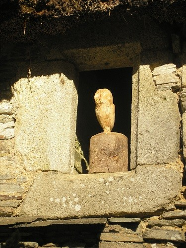 A carved owl in a niche in the wall of the walled garden.