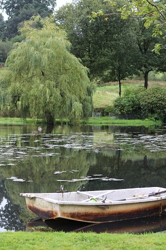 Behind the house is a large lake, complete with boat, a lovely tranquil scene.